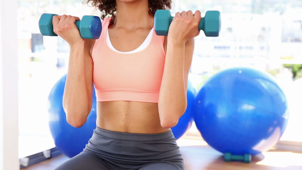 stock-footage-fit-woman-lifting-dumbbells-and-smiling-at-camera-at-the-gym